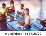 school kids meditating during... | Shutterstock . vector #568918120