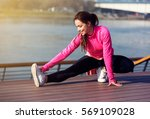 Woman Runner Stretching Legs...