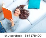 girl reads a book lying at... | Shutterstock . vector #569178400