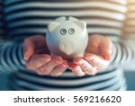 Small photo of Home budget concept with piggy coin bank in female hands