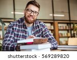 smiling young student sitting... | Shutterstock . vector #569289820