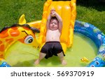 Small photo of A small boy happily plays in the blowup pool in his backyard, soaking up the sun and just relaxing.