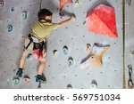 little boy climbing a rock wall ... | Shutterstock . vector #569751034
