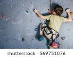 little boy climbing a rock wall ... | Shutterstock . vector #569751076