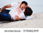 happy couple lying in the water ... | Shutterstock . vector #570082399