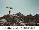 woman performs a handstand on a ... | Shutterstock . vector #570143476