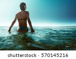 woman walks through shallow... | Shutterstock . vector #570145216