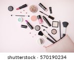 Stock photo a pink makeup bag with cosmetic beauty products spilling out on to a pastel colored background 570190234