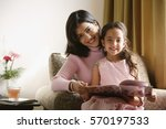 little girl sits on mother's... | Shutterstock . vector #570197533