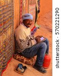 Small photo of Ait Benhaddou, Morocco - March 3, 2016: Man sits on the ground with artist supplies sketching and smiling in walled city of Ait Benhaddou, Morocco, Africa