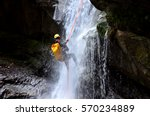 Small photo of Man hanging of a rope at the bottom of a waterfall