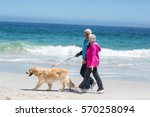 Stock photo cute mature couple walking their dog on the beach 570258094
