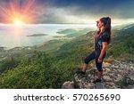hiker on top of a mountain.... | Shutterstock . vector #570265690