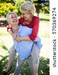 happy senior man giving a piggy ... | Shutterstock . vector #570369274