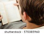 close up of a boy reading a book | Shutterstock . vector #570385960