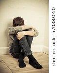 depressed boy sitting with head ... | Shutterstock . vector #570386050