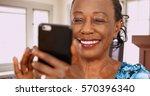 an elderly back woman swipes on ... | Shutterstock . vector #570396340
