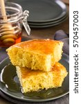 Stock photo slice of sweet cornbread with honey on the plate 570457003