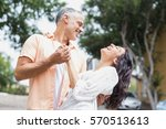 cheerful couple dancing against ... | Shutterstock . vector #570513613