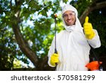 Portrait of smiling man showing thumbs up while holding insecticide sprayer in lawn - stock photo