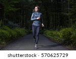 runner woman in a dark forest | Shutterstock . vector #570625729
