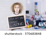 Small photo of Sad ADHD boy holding small board, shouting mother in background