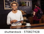 man using a tablet in a coffee... | Shutterstock . vector #570827428