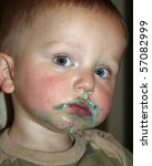 Male toddler with blue frosting around his mouth. - stock photo
