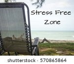 """Small photo of Holiday or relaxing concept with a view of fold able chair facing to the beach with message of """"Stress Free Zone"""""""