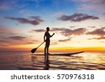 Small photo of paddle standing board, beach leisure activity, beautiful silhouette of man at sunset