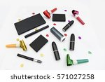 Assorted makeup items. Assorted makeup items arranged with party decorations on a white background - stock photo
