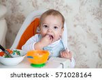 little baby boy eating sitting... | Shutterstock . vector #571028164