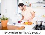 man looking recipe on laptop in ... | Shutterstock . vector #571219210
