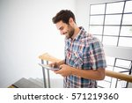 man using digital tablet at home | Shutterstock . vector #571219360