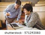 professor helping a student in... | Shutterstock . vector #571292083