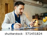 young businessman taking note... | Shutterstock . vector #571451824
