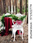 Small photo of Weeding decor. White forged chair with sigh Mrs. Decorated table served for two in pine forest. Decoration with marsala fabric, candles, candlesticks, wine bottles, flowers and grass. Bohemian style.