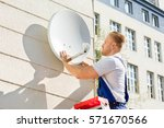 young man fitting tv satellite... | Shutterstock . vector #571670566