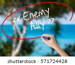 Small photo of Woman Hand Writing Enemy - Ally with black marker on visual screen. Isolated on nature. Business concept. Stock Photo