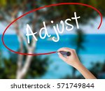 Small photo of Woman Hand Writing Adjust with black marker on visual screen. Isolated on nature. Business concept. Stock Photo
