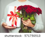 Stock photo handsome man holding bouquet of beautiful red roses in hand march woman day 571750513