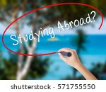 Small photo of Woman Hand Writing Studying Abroad? black marker on visual screen. Isolated on nature. Education, technology, internet concept. Stock Image