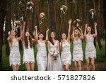 bride and bridesmaids throwing... | Shutterstock . vector #571827826