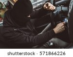 Car thief trying to start car with screwdriver in ignition. Car thief, car theft - stock photo