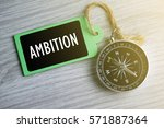 Small photo of Compass and wooden tag written with AMBITION on grey background.