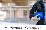 man holding his helmet in a... | Shutterstock . vector #572006998