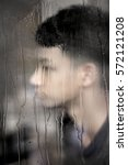Small photo of Absent mind teen in rainy day focus on raindrops on window.
