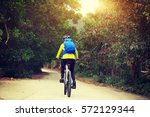 young woman riding mountain... | Shutterstock . vector #572129344