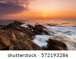 Sunset On The Rocky Shore Of A...