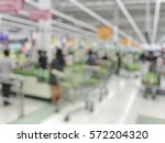Small photo of Blurred abstract background people waiting for paying products in shopping cart at the row of cashier counter checkout in the Supermarket store: Blurry view cashiers serves customers and trolley.